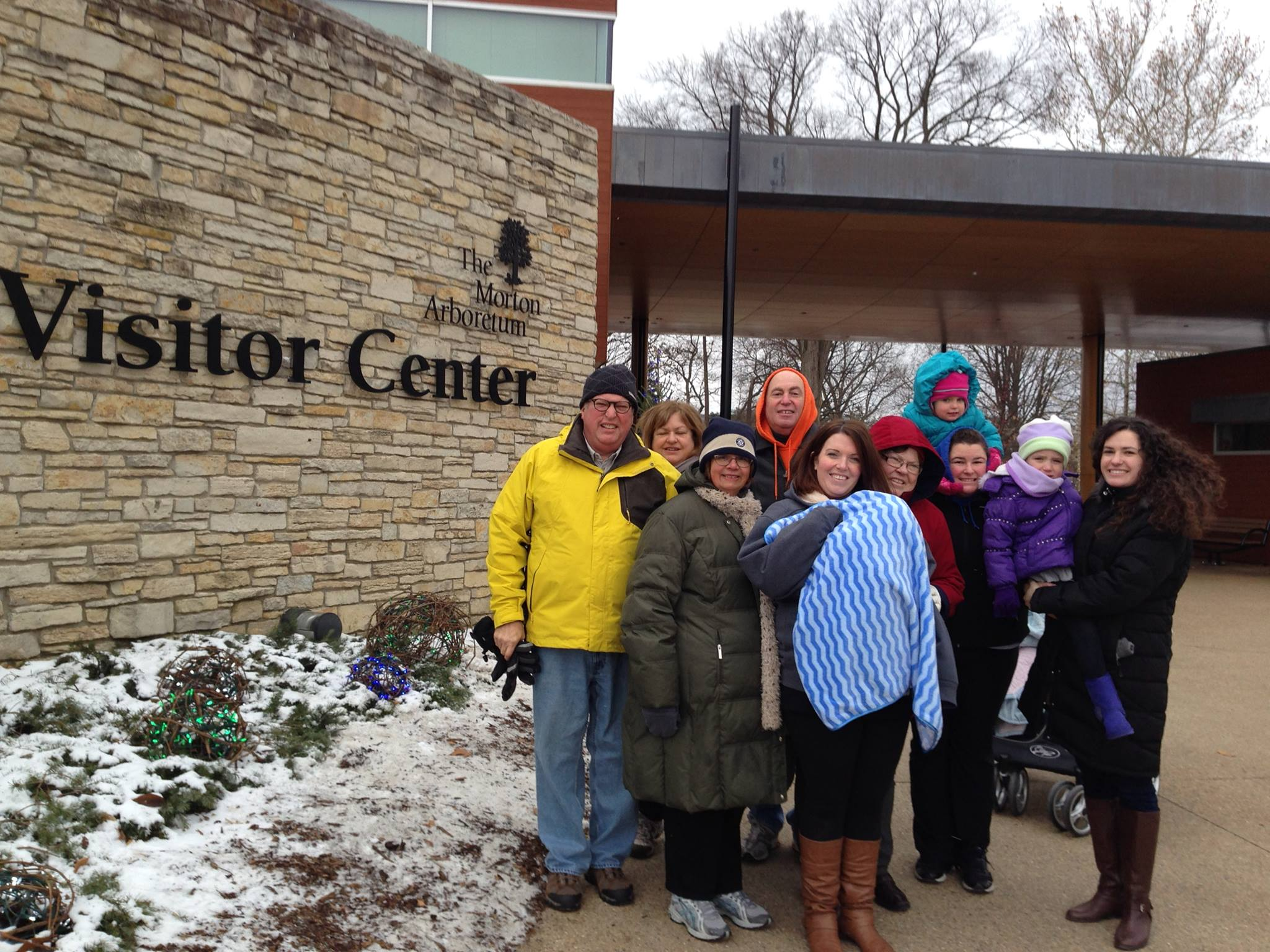 Family posing together in from of Visitor Center at The Morton Arboretum, with snow